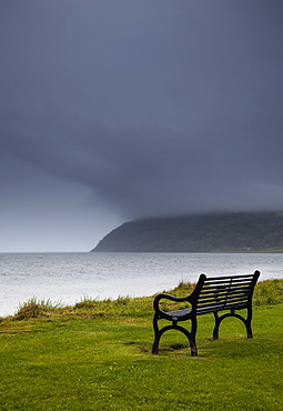 A bench at the water's edge with a dark stormy sky, Moray firth scotland