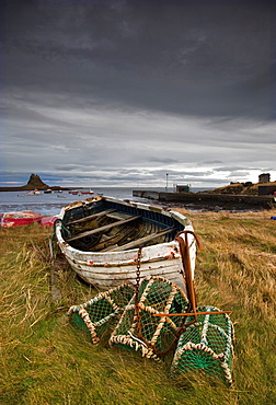 A Weathered Boat And Fishing Equipment Sitting On The Shore With Lindisfarne Castle In The Distance, Lindisfarne, Northumberland, England