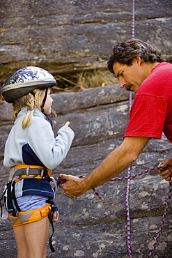 Mid-Aged Man Helping Daughter Tie Climbing Rope At Base Of Cliff, Near Rexford, Montana, Usa