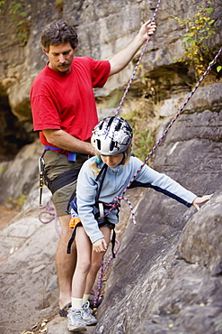 Young Girl (Age 7) Preparing To Climb While Father Belays At Stone Hills Near Rexford, Montana, Usa