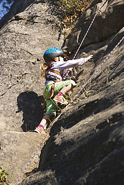 Young Girl (Age 5) Climbing On Granite Cliff At Stone Hills Near Rexford, Montana, Usa