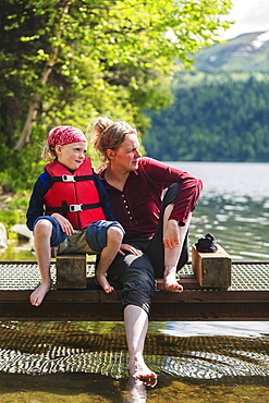 A Mother And Daughter Sits On A Dock Looking Out Over Byers Lake, Soaking Their Bare Feet In The Water, Denali State Park, Alaska, United States Of America