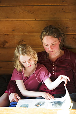 A Mother And Daughter Sitting Together Reading A Book, Leaning Against A Wooden Cabin Wall, Alaska, United States Of America