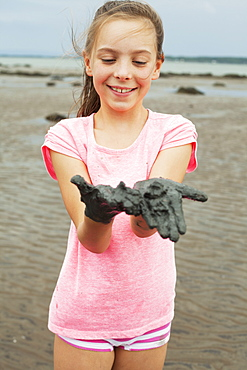 Young Girl Wearing Pink On A Shore Showing Her Muddy Hands, Charlevoix, Quebec, Canada
