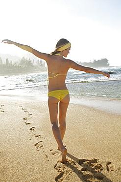 A Young Woman In A Yellow Bikini Walks On The Wet Beach Along The Water's Edge, Kauai, Hawaii, United States Of America