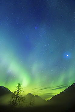 Northern Lights In The Sky Above Moose Pass, With Silhouetted Kenai Mountains In The Fog And Low Cloud, Chugach National Forest, Moose Pass, Alaska, United States Of America