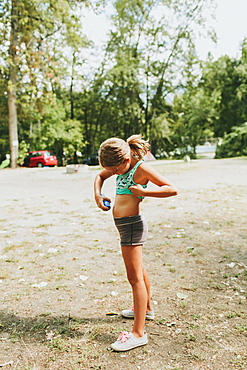 A Young Girl Applies Sunscreen On Her Skin, Peachland, British Columbia, Canada