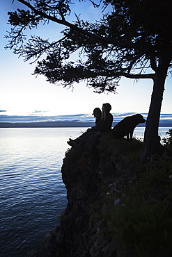 A Couple With A Dog Sit On A Ridge At The Water's Edge Looking Out Over Halibut Cove, Kachemak Bay, Kenai Peninsula, Alaska, United States Of America