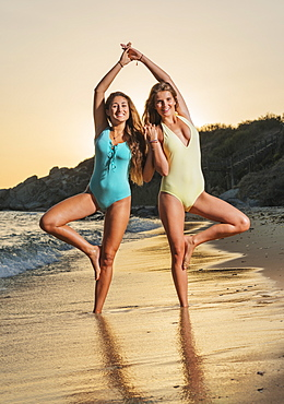 Two Young Women In Bathing Suits Posing On The Beach At Sunset, Tarifa, Cadiz, Andalusia, Spain