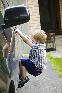 A Young Boy Playing On A Car, Guelph, Ontario, Canada