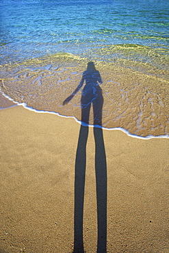 Shadow Of A Woman Standing On The Beach At The Water's Edge, Kauai, Hawaii, United States Of America