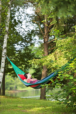Girl Sleeping In Hammock With Headphones, Ontario, Canada