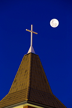 Close Up Of Church Steeple With Cross At Night With Full Moon In A Deep Blue Sky, Calgary, Alberta, Canada