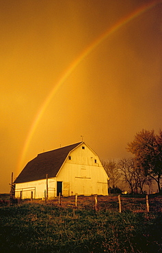 Agriculture - A rainbow arcs over a gambrel roof barn in dramatic stormy light / Northwest Missouri, USA.