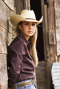 Agriculture - Portrait of a young cowgirl leaning against an old barn / Childress, Texas, USA.