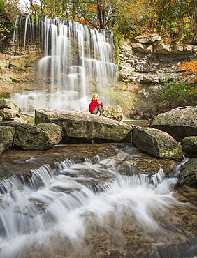 Young Boy Sitting On A Rock Watching The Falls At Rock Glen Conservation Area, Ontario, Canada