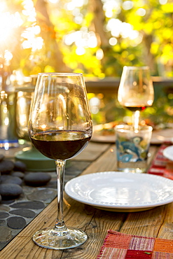 Glasses Of Red Wine On A Table Set For A Meal, Ontario, Canada