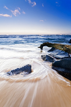 Surf Washing Up Around Driftwood And Rocks, Wailua, Kauai, Hawaii, United States Of America