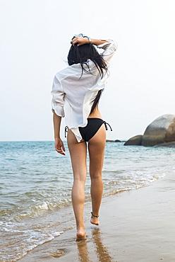 Young Woman Walking On The Beach In A Bikini, Xiamen, China
