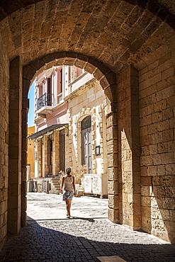 A Woman Walks Through An Arched Walkway, Chania, Crete, Greece