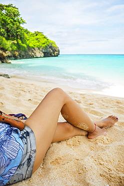The Legs Of A Girl Sitting On The Sand Of Puka Beach, Borakay, Panay, Philippines