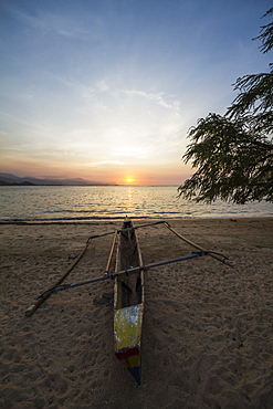 Outrigger Boat On An Areia Branca Beach At Sunset, Dili, East Timor