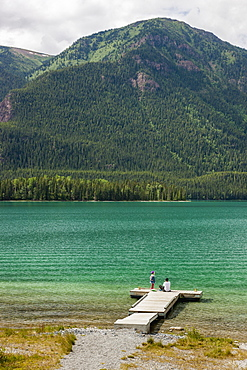 Mother And Daughter On A Dock At Muncho Lake Provincial Park, British Columbia, Canada, Summer
