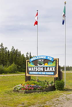 A Welcome To Watson Lake Sign With Flags In The Background, Yukon Territory, Canada, Summer