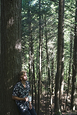 Young Man Standing In A Forest With A Cup Of Coffee, Little River State Park, Waterbury, Vermont, United States Of America