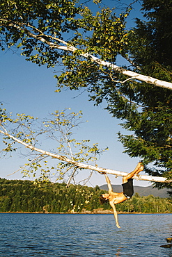A Young Man Hanging On To A Tree Branch Leaning Out Over A Lake, Waterbury, Vermont, United States Of America