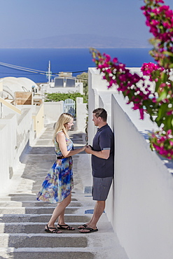 A Couple Stands On A Walkway By A Whitewash Wall On A Greek Island, Santorini, Greece