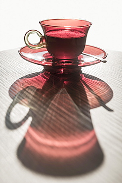 A Red Glass Cup A Saucer With A Beverage Reflected On A White Surface, Locarno, Ticino, Switzerland