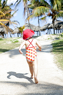 Child Running Down A Path Barefoot Towards The Beach, Varadero, Cuba