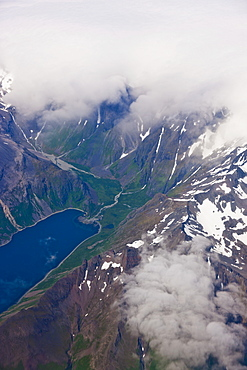 Aerial View Of Clouds Obscuring Peaks With A Lush Green Valley And Lake Visible In The Foreground, Aleutian Range, Alaska Peninsula, Southwestern Alaska, USA, Summer