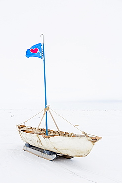 A White Umiak Skin Boat Sits On Skids On The Sea Ice With A Flag Flying Above The Boat, Barrow, North Slope, Arctic Alaska, USA, Winter