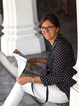 Woman Sitting On A Step Looking At A Map, Bangkok, Thailand