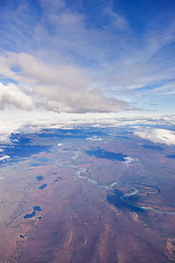 Aerial View Of Patchy Clouds Above A Tundra Landscape, A River Cutting Through The Foreground, Alaska, United States Of America