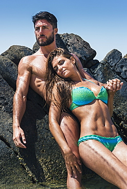 A Couple In Swimwear Leaning Against A Rock At The Coast, Tarifa, Cadiz, Andalusia, Spain