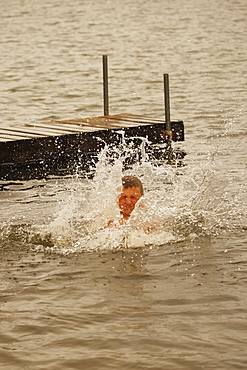 Boy In Water After Jumping Off Dock In A Lake