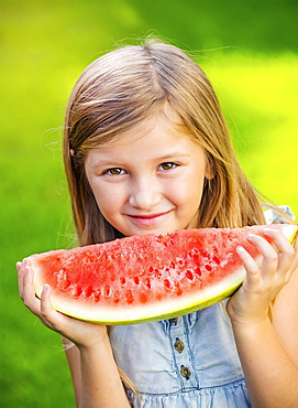 Adorable Cute Little Girl Eating Watermelon On The Grass In Summertime