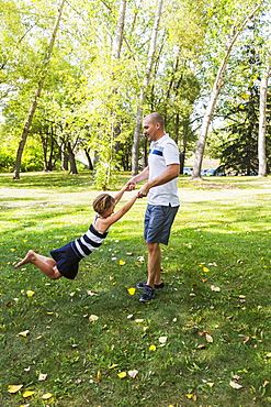A Father Swinging His Daughter Around In A Park During A Family Outing, Edmonton, Alberta, Canada