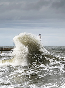 Large Wave Crashing At The Coast With A Lighthouse At The End Of A Pier, Amble, Northumberland, England