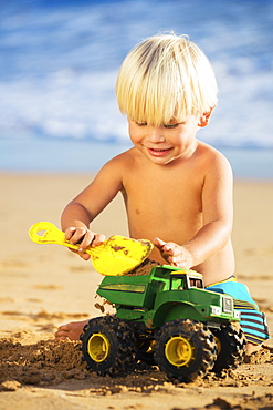 Happy Young Boy Playing With Toys At The Beach