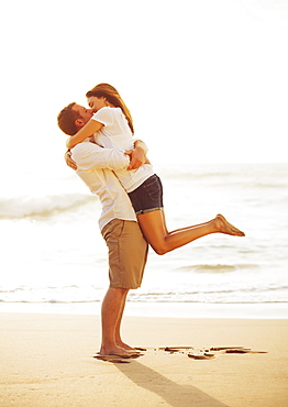 Happy Romantic Couple Kissing On The Beach At Sunset