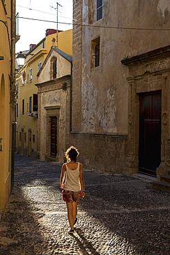 Girl Walking Down A Cobblestone Alley Between Buildings, Alghero, Sardinia, Italy