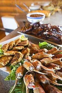A Spread Of Crab Claws, Crab Cakes And Barbecue Ribs Awaits Guests At The Katmai Wilderness Lodge In Kukak Bay, Katmai National Park & Preserve, Alaska.