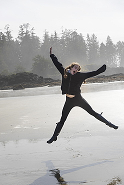 A Girl Leaping In Mid-Air On A Wet Beach, Tofino, British Columbia, Canada