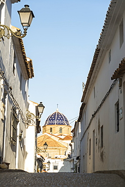 Street In Downtown Altea, A Beautiful Town In Costa Blanca, With The Cupule Of The Church In The Background, Altea, Alicante, Spain