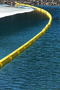 Yellow Buoy Across The Water With Rocky Shoreline And Ice On Lake, Kananaskis Country, Alberta, Canada