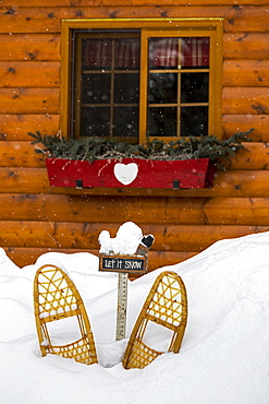 Old Wooden Snowshoes In Snow In Front Of Log Cabin Window With Flower Box, Lake Louise, Alberta, Canada